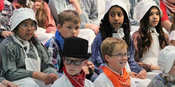 Children in pioneer costumes.