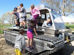 Kids climbing around a small amphibious vehicle