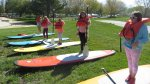 Kids standing on paddle-boards on the lawn.