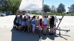 Kids standing around a sailboat.