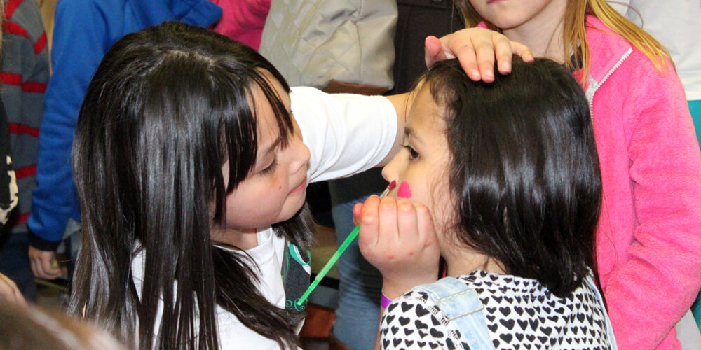 Young girl painting another child's face.