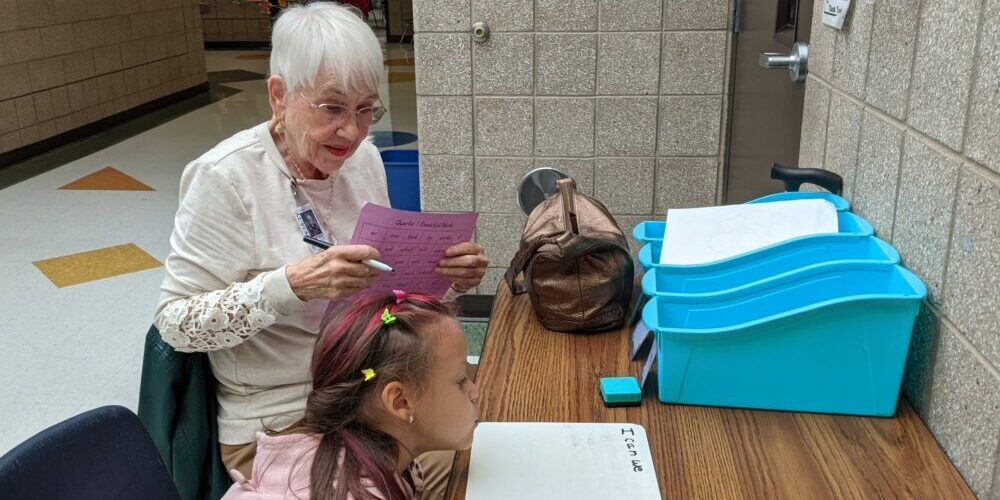Foster Grandmother teaching sight words to young child.